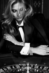 Stoere vrouwelijke smoking met zijde revers en beklede knopen. Witte maatblouse met blinde sluiting en zwarte strik